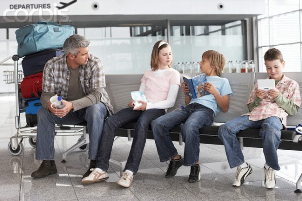 Father and three kids sitting in airport